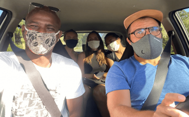 people in a car with masks during corona